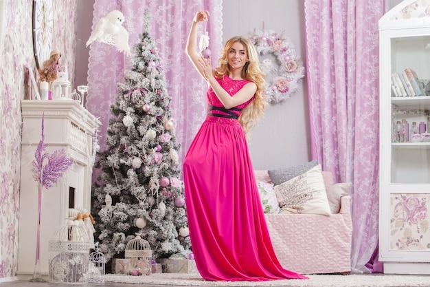 Piękna, młoda dziewczyna z długimi falującymi włosami w różowej sukience trzymając choinkę