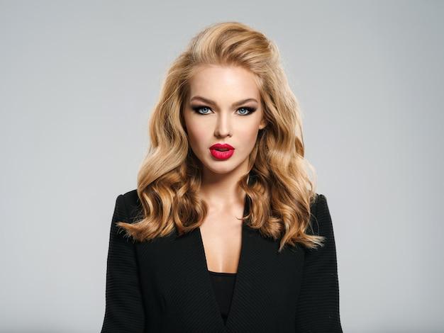 Piękna, młoda dziewczyna z długimi włosami nosi czarną kurtkę. modelka pozuje