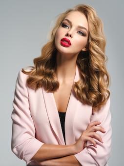 Piękna, młoda dziewczyna z długimi włosami nosi różową kurtkę. modelka pozuje