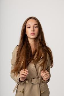 Piękna młoda dziewczyna z długimi włosami pozowanie na szarej ścianie, moda, uroda, makijaż, kosmetyki, salon piękności, styl, higiena osobista, postawa.