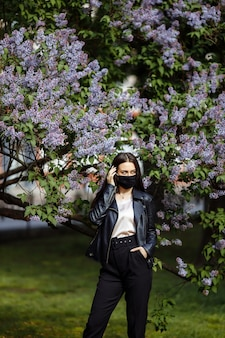 Piękna, młoda dziewczyna z długimi włosami w letnim ogrodzie bzu z kwiatami