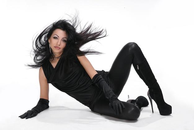 Piękna, młoda dziewczyna z dmuchaniem włosów w czarnej sukni na białym tle