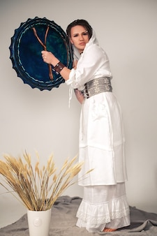 Piękna, młoda dziewczyna z dredami w stylu boho. z etnicznym bębnem w dłoni. odpoczynek medytacji