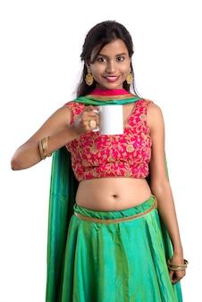 Piękna młoda dziewczyna z filiżanką herbata lub kawa pozuje na biel powierzchni