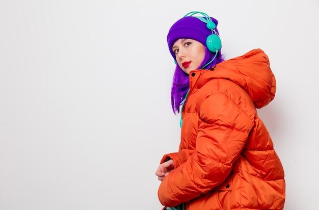 Piękna, młoda dziewczyna z fioletowymi włosami iw pomarańczowej kurtce słuchać muzyki w słuchawkach.