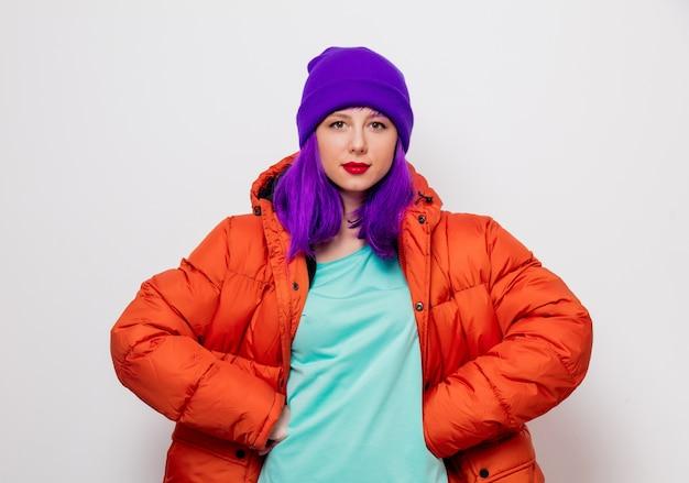 Piękna, młoda dziewczyna z fioletowymi włosami iw pomarańczowej kurtce.