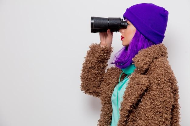 Piękna, młoda dziewczyna z fioletowymi włosami w kurtce, patrząc w lornetkę.