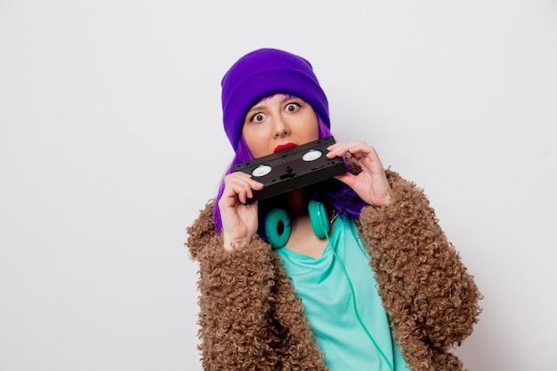 Piękna, młoda dziewczyna z fioletowymi włosami w kurtce trzymając kasetę vhs.