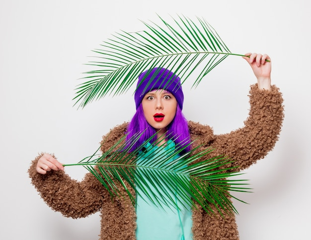 Piękna, młoda dziewczyna z fioletowymi włosami w kurtce z liściem palmowym.