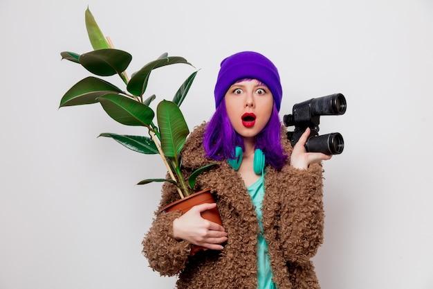 Piękna, młoda dziewczyna z fioletowymi włosami w kurtce z lornetką i rośliną.