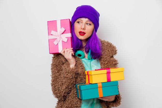 Piękna, młoda dziewczyna z fioletowymi włosami w kurtce z pudełka na prezenty świąteczne.
