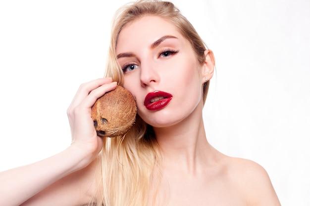 Piękna młoda dziewczyna z kokosem w dłoni
