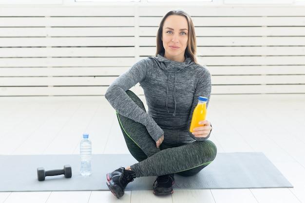Piękna, młoda dziewczyna z koktajl fitness, butelka wody i hantle