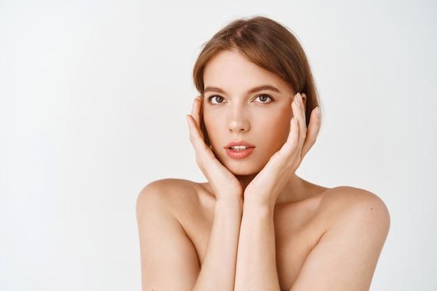 Piękna młoda dziewczyna z lekkim naturalnym makijażem i idealną skórą, dotykając twarzy i zmysłowego wyglądu. kobieta z nagimi ramionami nakładająca kosmetyki do pielęgnacji ciała, biała ściana