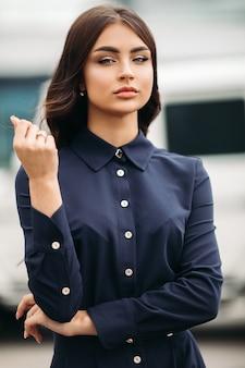 Piękna młoda dziewczyna z makijażem elegancko prostuje dłonią swoje długie kasztanowe włosy