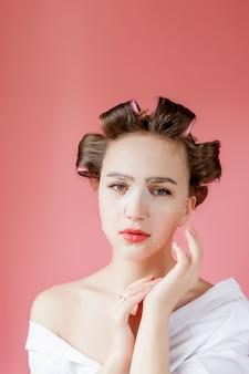 Piękna młoda dziewczyna z maską i curlers dotyka jej twarz.