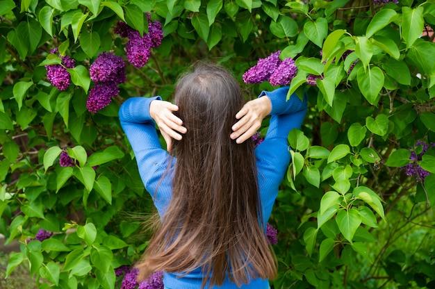 Piękna młoda dziewczyna z pięknymi włosami w pobliżu bzu.