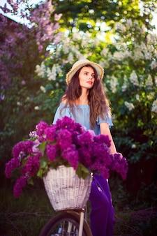 Piękna młoda dziewczyna z rocznika bicyklem i kwiaty na miasto scenie w świetle słonecznym plenerowym.