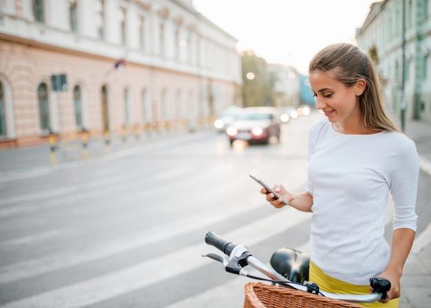 Piękna młoda dziewczyna z rowerem za pomocą telefonu w mieście.
