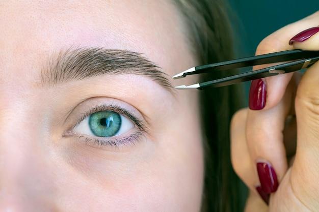 Piękna młoda dziewczyna z rzęsami pęsetą jej brwi w salonie piękności. kobieta robi korektę makijażu permanentnego brwi. microblading brwi.