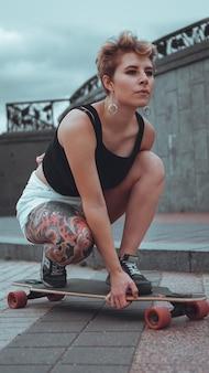 Piękna, młoda dziewczyna z tatuażami siedzi na longboardzie. ma tradycyjny japoński tatuaż