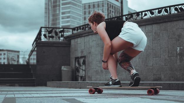 Piękna, młoda dziewczyna z tatuażami siedzi na longboardzie