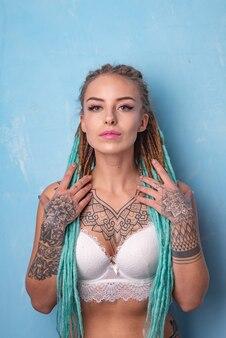 Piękna młoda dziewczyna z tatuażem i dredami pozuje w białym biustonoszu