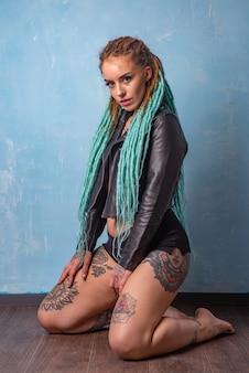 Piękna młoda dziewczyna z tatuażem i dredami pozuje w czarnej skórzanej kurtce