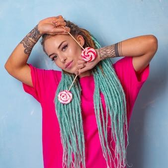 Piękna młoda dziewczyna z tatuażem i dredami pozuje w różowej koszulce z cukierkami lizaki