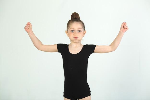 Piękna, młoda dziewczyna zaangażowana w gimnastykę na białej ścianie