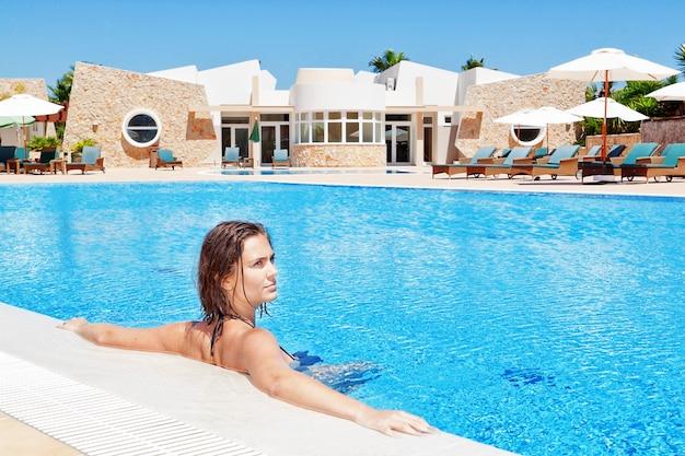 Piękna młoda dziewczyna zanurzona w basenie relaksujący. w wodzie w lecie.