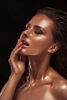 Piękna młoda dziewczyna zbliżenie z błyszczącą skórą i brązowym kolorem. ciemne włosy, profesjonalny makijaż, czysta skóra.