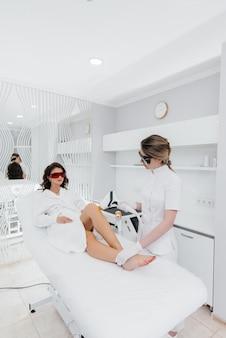 Piękna młoda dziewczyna zostanie poddana depilacji laserowej na nowoczesnym sprzęcie w salonie spa. salon piękności. pielęgnacja ciała.
