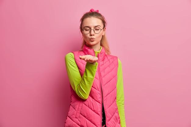 Piękna młoda europejka dmucha pocałunek w powietrze, trzyma dłoń do przodu, aparat zamyka oczy, wyraża romantyczne uczucia