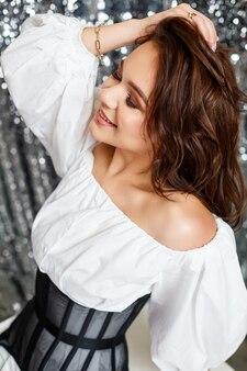 Piękna młoda europejka ubrana w czarny gorset, białą koszulę. seksowna kobieta z profesjonalnym makijażem na twarzy.