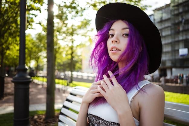 Piękna młoda fioletowa włochata dziewczyna spaceru o zachodzie słońca w parku miejskim. st. petersburg, nowa holandia