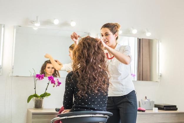 Piękna młoda fryzjerka daje nową fryzurę klientce w salonie.