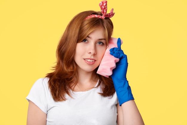 Piękna młoda gospodyni domowa w przypadkowych ubraniach i gumowych rękawiczkach ochronnych, trzyma gąbkę przy uchu, udaje, że rozmawia przez telefon komórkowy, ma zadowolony wyraz twarzy i uśmiech, na żółtym tle