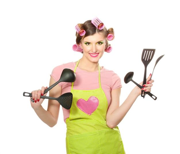Piękna młoda gospodyni z naczynia kuchenne na białym tle