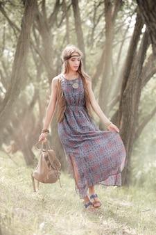 Piękna młoda hipis kobieta stojąca wśród drzew w parku