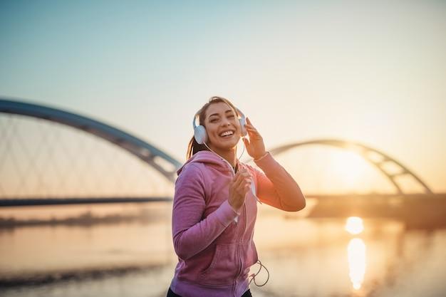 Piękna młoda i sprawna kobieta w dobrej kondycji bieganie i jogging samotnie na ulicy mostu miasta.