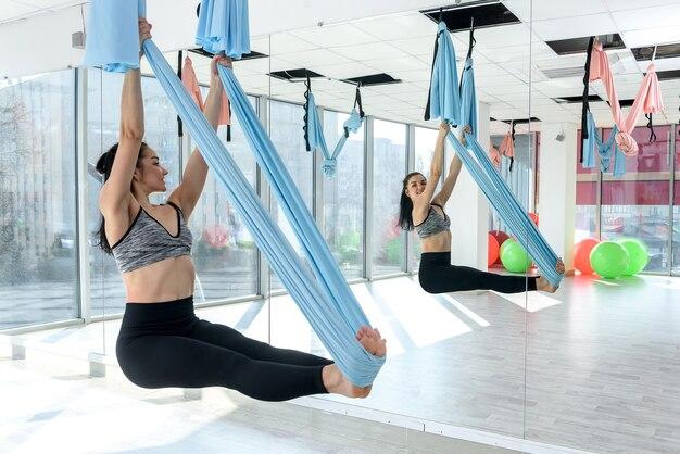 Piękna młoda instruktorka ćwiczy jogę latania w hamaku na siłowni. ćwiczenia dla relaksu lub zdrowia