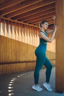 Piękna młoda instruktorka fitness prowadzi lekcje wideo za pomocą laptopa na drewnianej werandzie na ulicy.