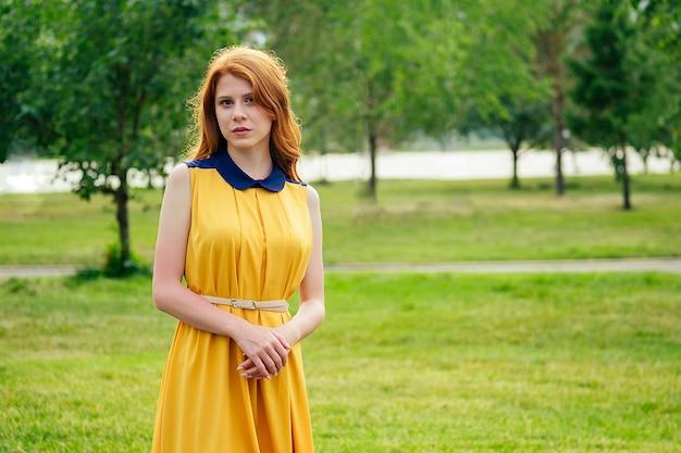 Piękna młoda irlandzka ruda ruda kobieta w żółtej sukience stylowe w letnim parku. koncepcja świeżości i kobiecości