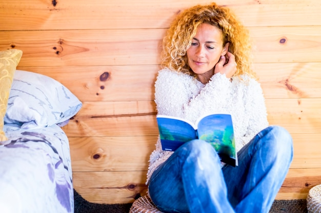 Piękna młoda kaukaska blondynka kręcona kobieta lubi czytać papierową książkę w domu, siedząc na podłodze z drewnianym łóżkiem walland po jej stronie kryty wypoczynek koncepcja relaksu