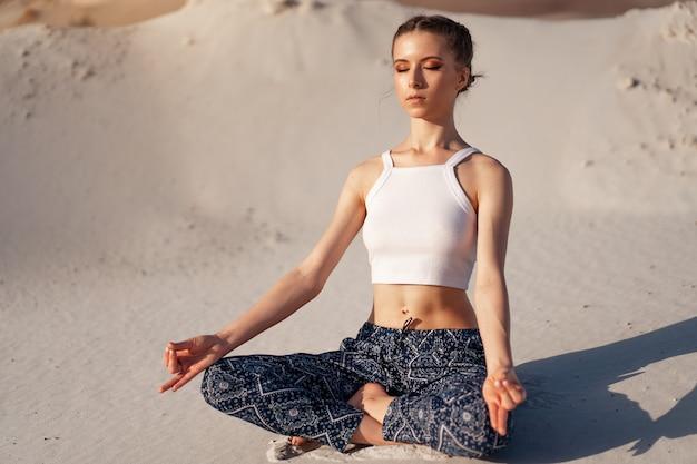 Piękna młoda kaukaska dziewczyna w białej bluzce i szerokich spodniach siedzi w pozycji lotosu na plaży na piasku. najpopularniejsza poza do medytacji.
