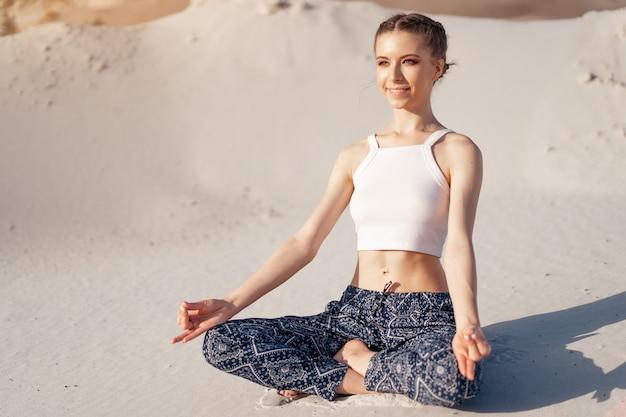Piękna młoda kaukaska dziewczyna w białej bluzce i szerokich spodniach siedzi w pozycji lotosu na plaży na piasku.