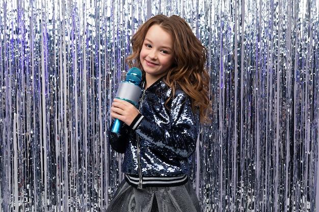 Piękna młoda kaukaska dziewczyna z mikrofonem na ścianie świecidełka