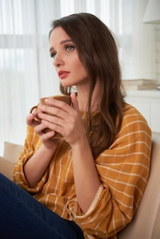 Piękna młoda kaukaska kobieta siedzi na kanapie w domu z filiżanką herbata