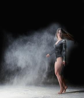 Piękna młoda kaukaska kobieta w czarnym body o sportowej sylwetce tańczy w białej chmurze mąki na czarnym tle